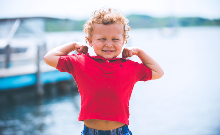 Curly-haired boy in a red polo smiles as he flexes his arms in a power pose by a lake