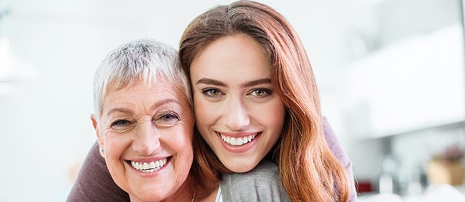 An older woman with a dental bridge smiling with her daughter.