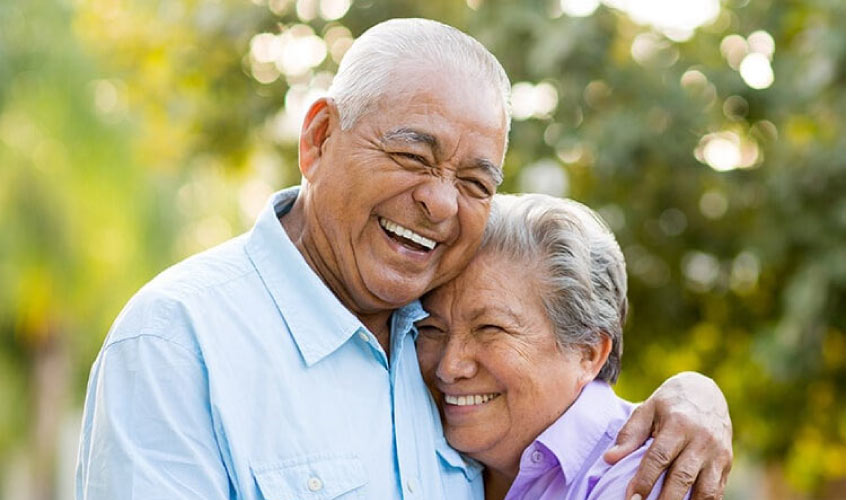 senior couple hugging and smiling after oral health exams