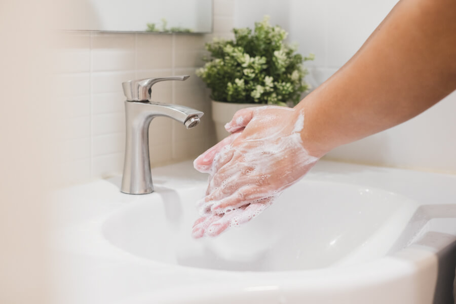 Closeup image of person washing their hands to protect themselves from coronavirus