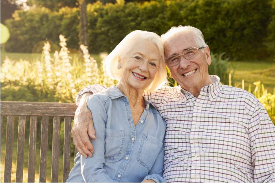 senior couple sitting on a bench hug and smile after learning about caring for their dentures
