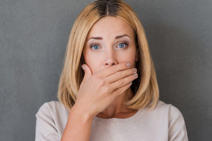woman covering her mouth with her hand to hide early gum disease