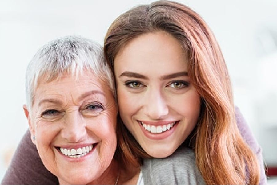 a young woman and a senior woman smile together after learning about dental bridges