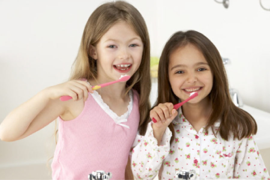 two young girls excited about oral health brush their teeth together