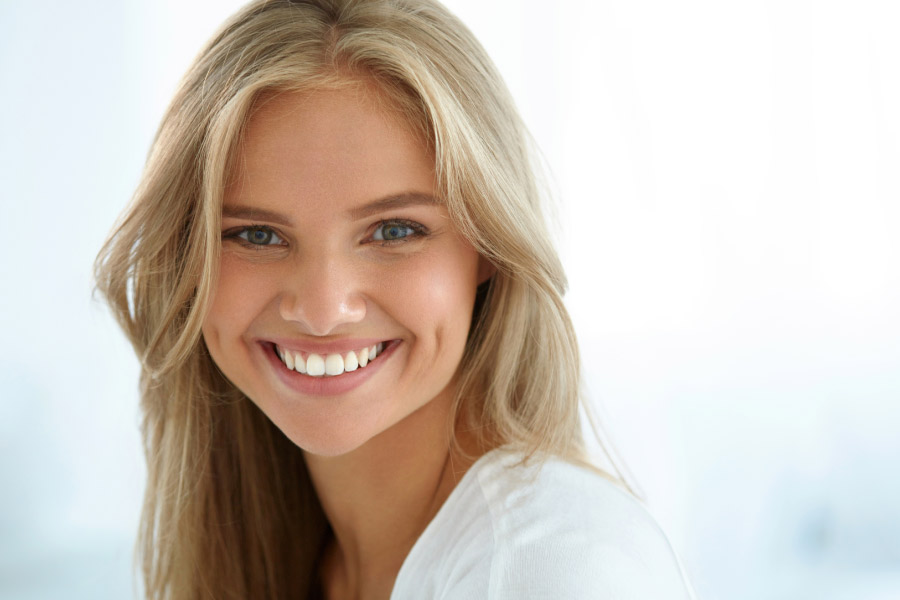 young woman flashes a brilliant smiles after professional teeth whitening