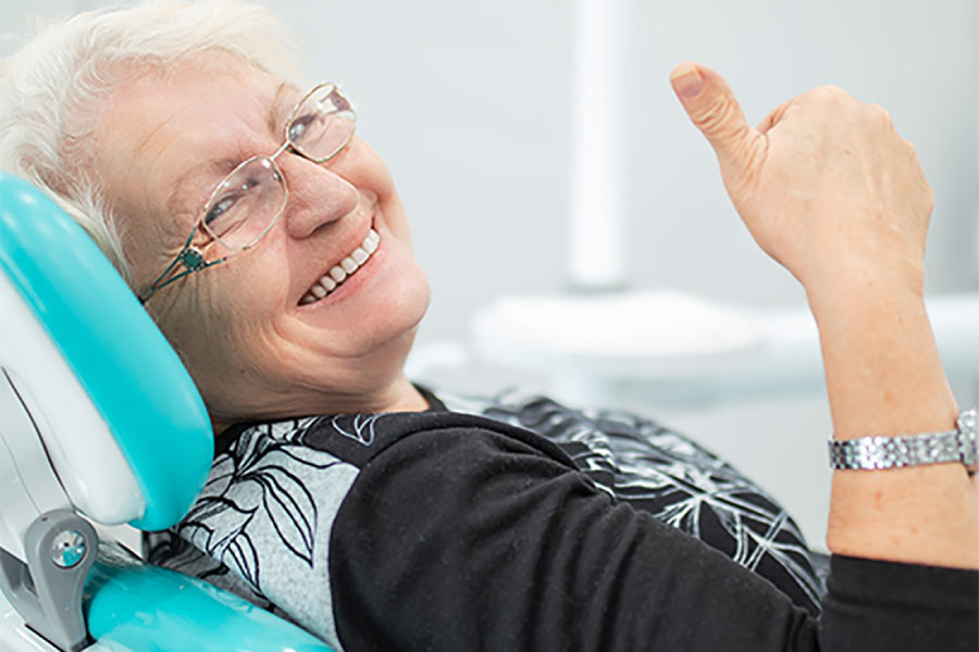 senior women in the dentist chair gives a thumbs up after learning about teeth replacement options