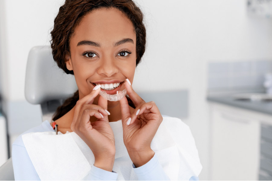 young women gets ready to insert Invisalign clear aligner